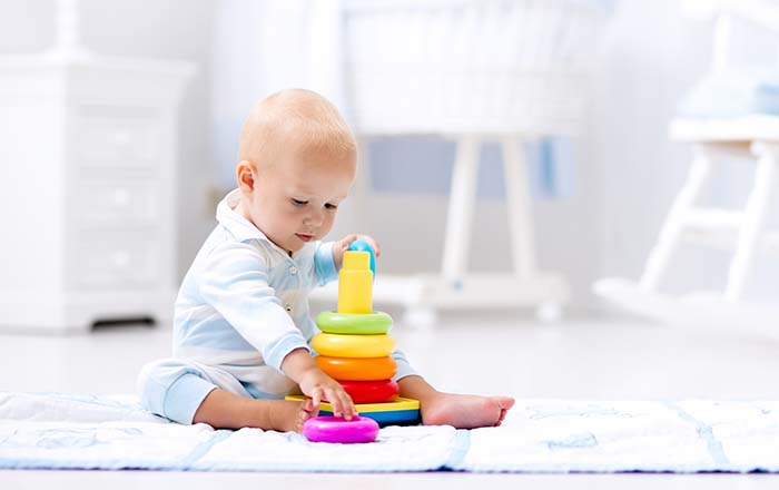 Baby playing with plastic puzzle toy